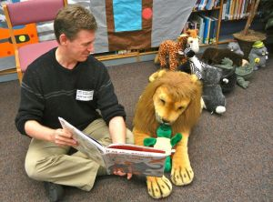 The author reading one of his picture books to a library lion